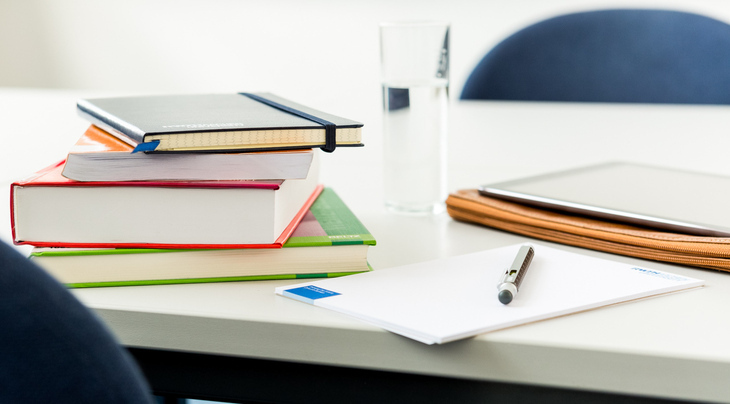 Books, tablet and pen lying on a table